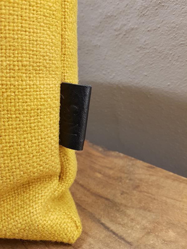 gul pude med læderdetalje